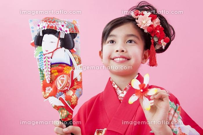 羽子板を持って微笑む女児の販売画像