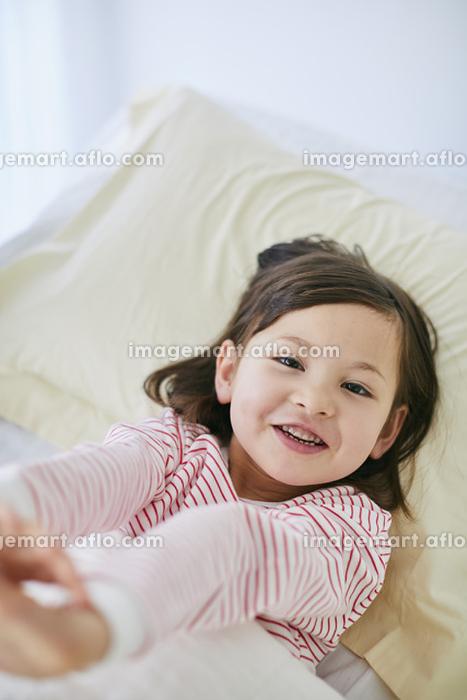 ベッドで伸びをするハーフの子供