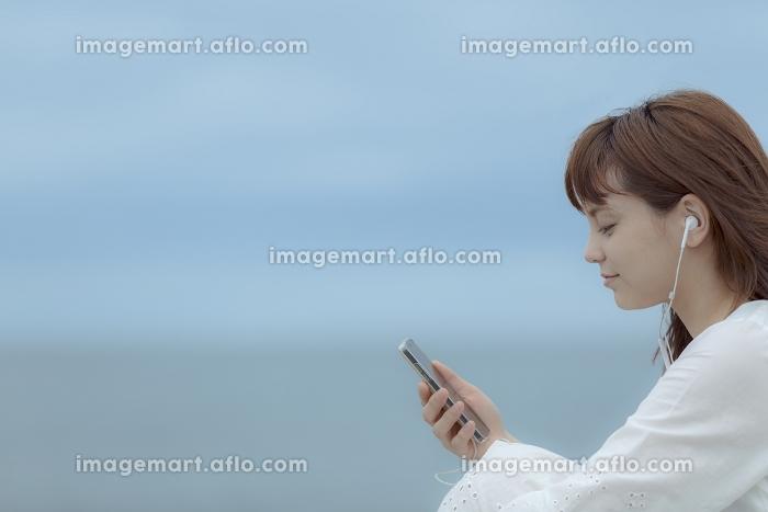 スマートフォンで音楽を聴く日本人女性の販売画像