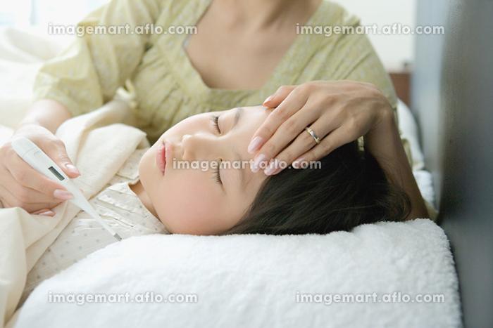 お母さんに熱を計られる女の子の販売画像
