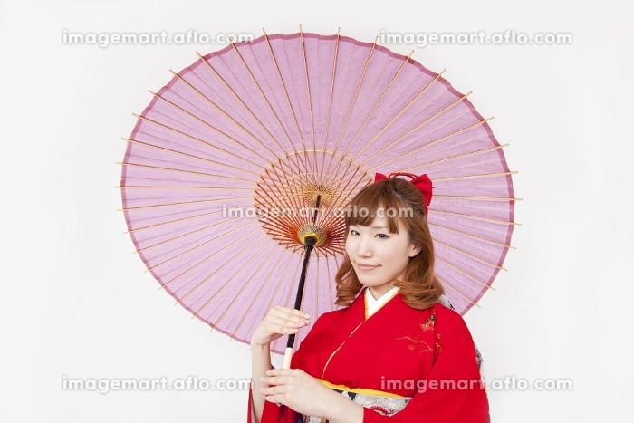 和傘を差し微笑む振袖姿の女性の販売画像