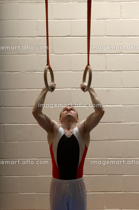 Male gymnast hanging from ringsの販売画像