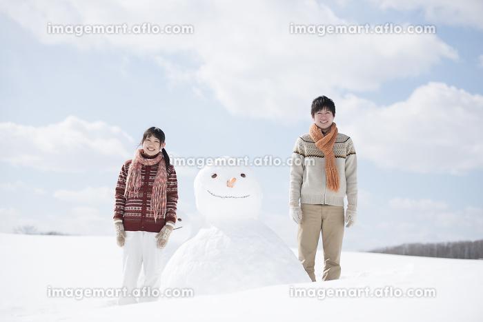 雪だるまの側で微笑むカップルの販売画像