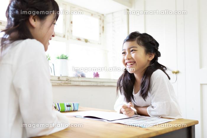 勉強する娘とそれを見る母親