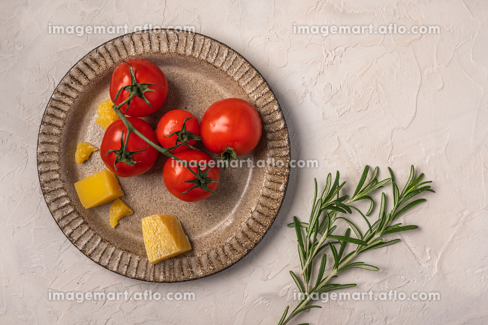 Cherry tomatoes, parmesan cheese on a ceramic plate and rosemary twigの販売画像