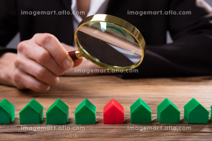 Businessperson Holding Magnifying Glass Over House Modelの販売画像