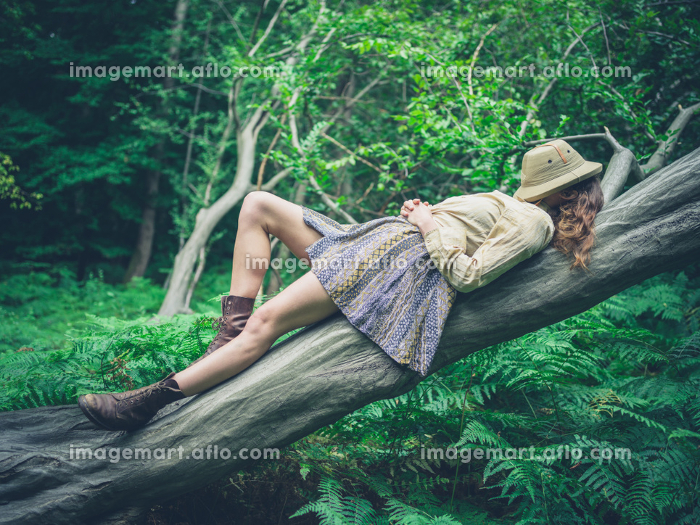 A young woman is lying on a fallen tree in the forest surrounded by ferns with a safari hat covering her face