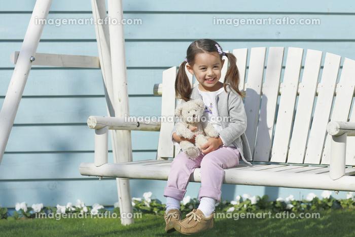 庭の白いブランコに座る小さな女の子の販売画像