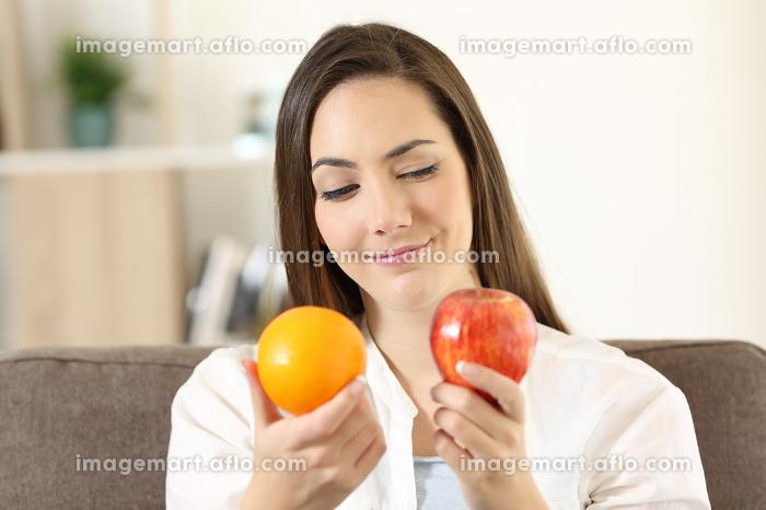 Girl deciding between two fruitsの販売画像