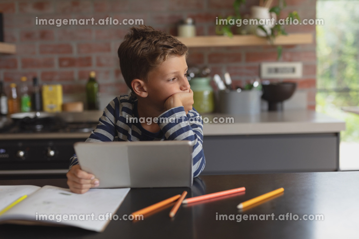 Side view of adorable Caucasian boy using digital tablet at table in kitchen at homeの販売画像