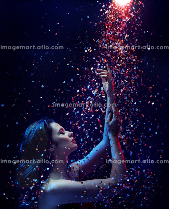 Portrait of a brunette lady taking a sequin showerの販売画像
