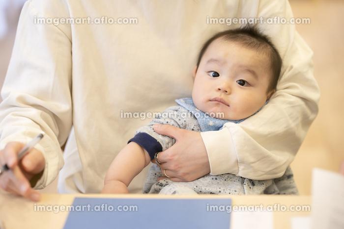 デスクワークをするお母さんに抱かれる赤ちゃんの販売画像
