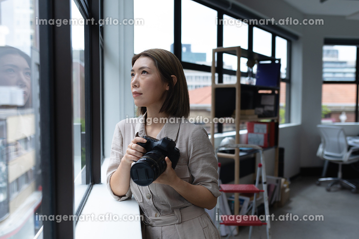 Asian businesswoman holding camera looking through window in creative office. social distancing in workplace during covid 19 pandemic.の販売画像