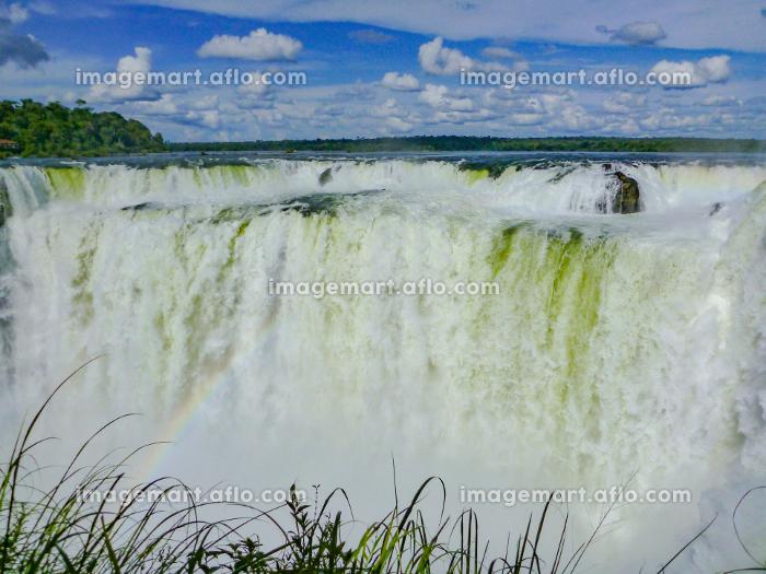 アルゼンチン・ブラジル国境エリアのイグアスの滝にて虹のかかった悪魔の喉笛と青空の販売画像