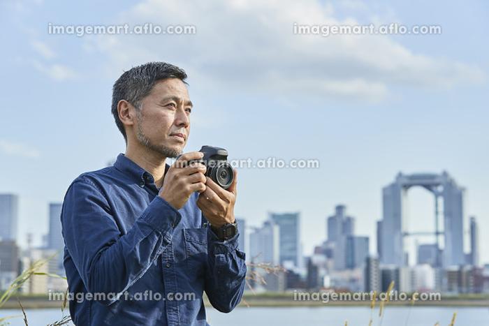 写真を撮る日本人男性の販売画像