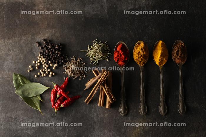 暗い背景に置いた香辛料とスプーンに乗せた香辛料の販売画像