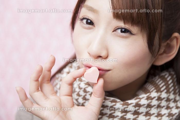 ハート型チョコにキスをする女性の販売画像