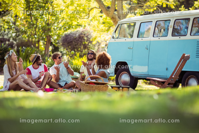 Group of friends having fun together near campervanの販売画像