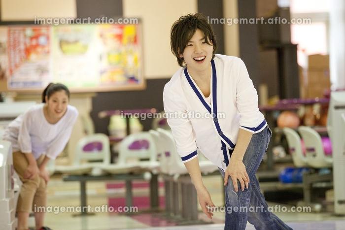 ボウリングをする男性と見つめる女性の販売画像