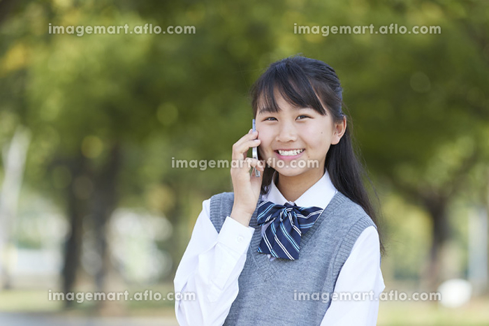 新緑とスマホで通話する女子中学生