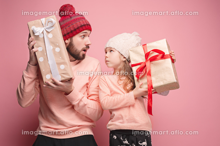 Portrait of a surprised little girl with her father holding a Christmas presentの販売画像