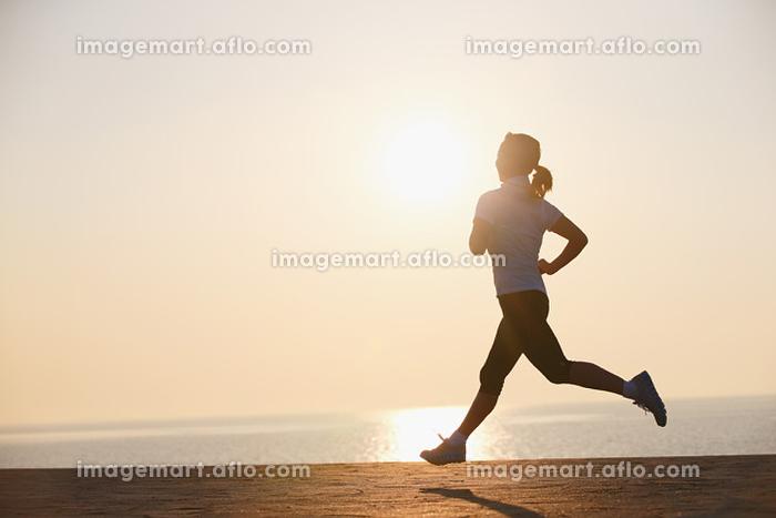 太陽とジョギングする女性の販売画像