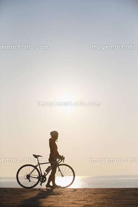 太陽と休憩するサイクリングの女性
