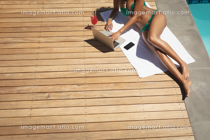 Low section of young African American woman using laptop in her backyard on a sunny dayの販売画像