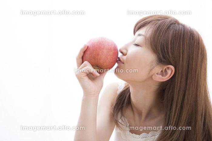 リンゴにキスをする女性の販売画像
