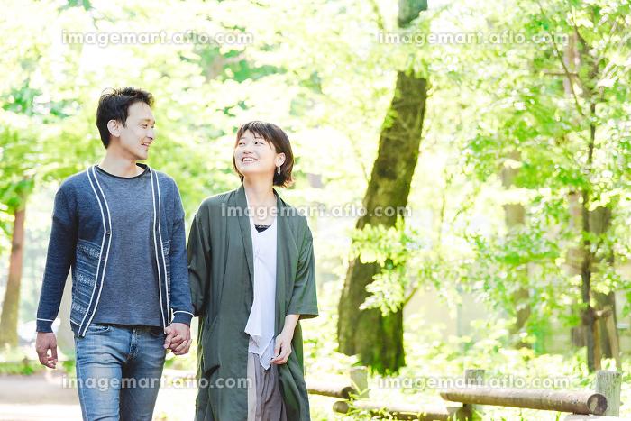 緑の豊かな公園でデートをするカップルの販売画像