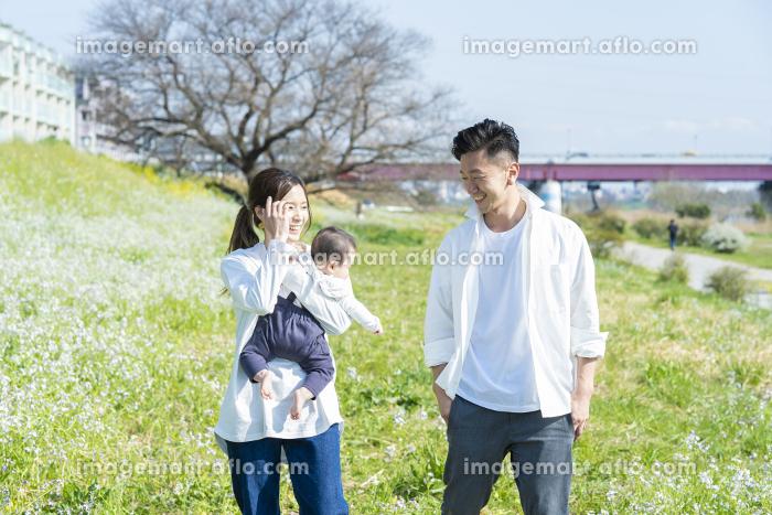 赤ちゃんを抱っこして散歩する夫婦の販売画像