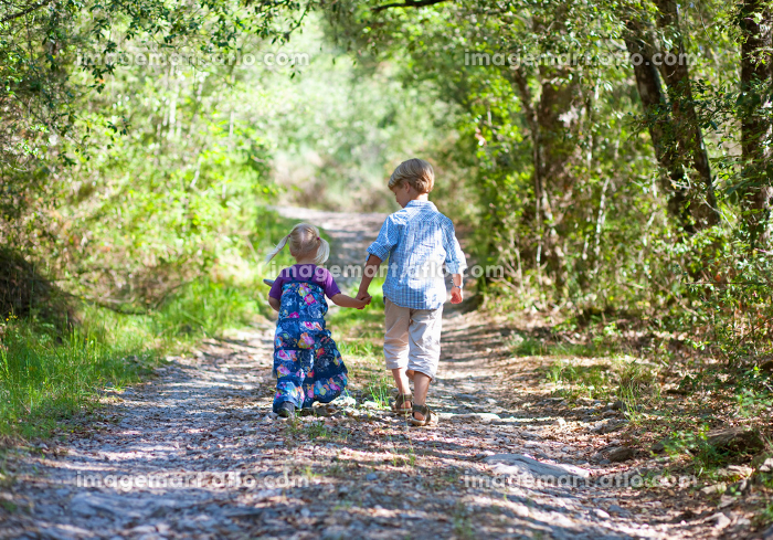Children walking hand-in-hand outdoorsの販売画像