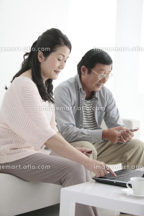 ネットショッピングをするシニア夫婦の販売画像