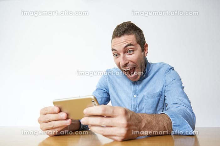 スマートフォンを見る外国人男性の販売画像