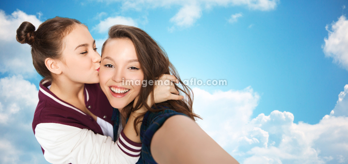 happy teenage girls taking selfie and kissingの販売画像