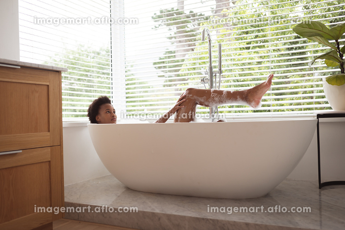Mixed race woman spending time at home self isolating and social distancing in quarantine lockdown during coronavirus covid 19 epidemic, taking a foamy, warm bath and relaxing.の販売画像