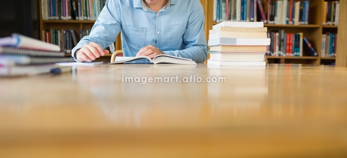 Mid section of a mature male student studying at desk in the libraryの販売画像