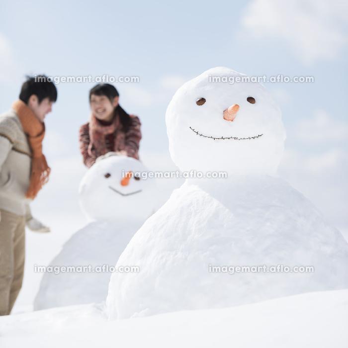 雪だるまを作るカップルの販売画像