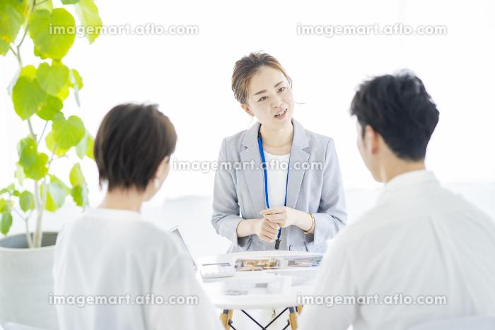 夫婦に不動産を営業するスーツ姿の女性の販売画像