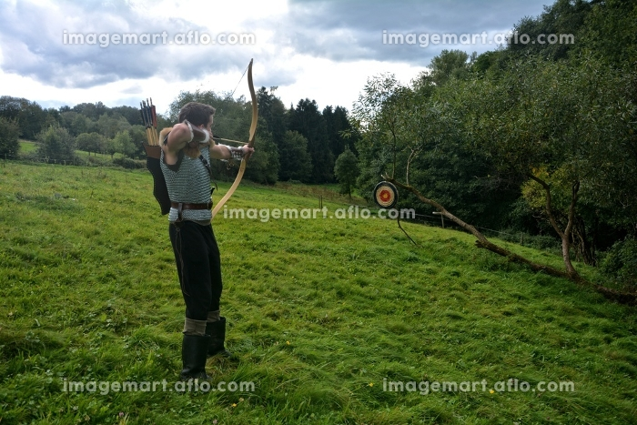 medieval archer,aiming with bow and arrow at straw disc in natureの販売画像