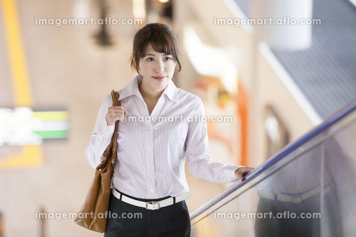 エスカレーターに乗る女性の販売画像