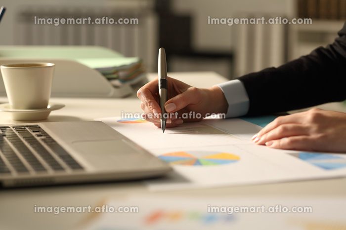 Business woman hands writing on report at nightの販売画像