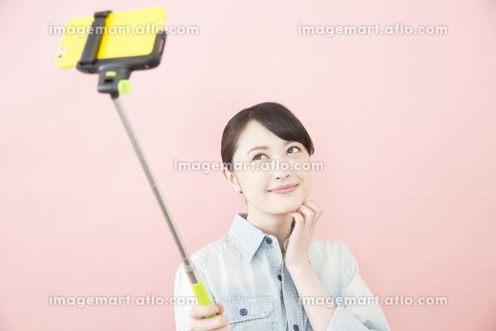 セルカ棒で自撮りをする女性の販売画像