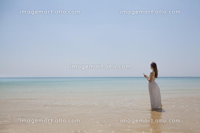波打ち際でスマートフォンを持って立つ日本人女性の販売画像