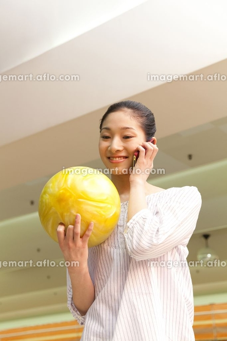 ボウリング球を持って電話する女性の販売画像