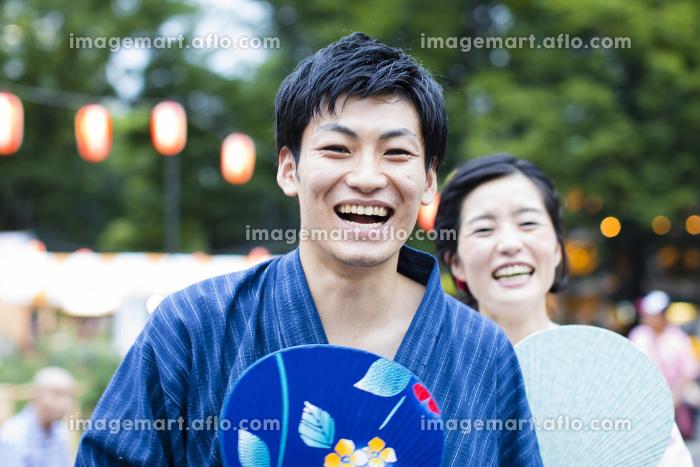お祭りを楽しむ浴衣姿のカップルの販売画像