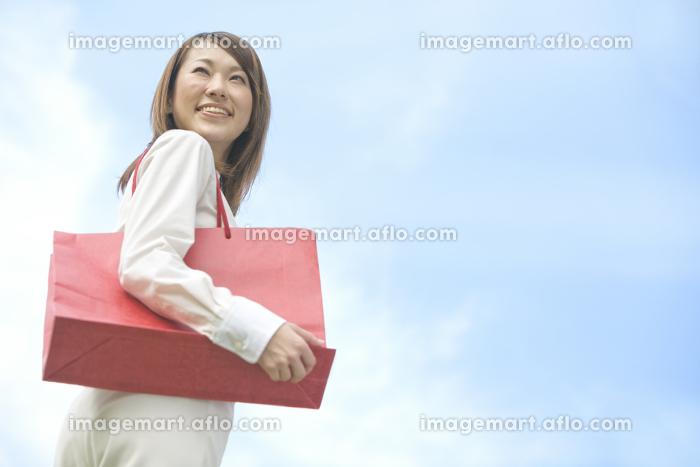 青空の下で買い物袋を持つ女性の販売画像