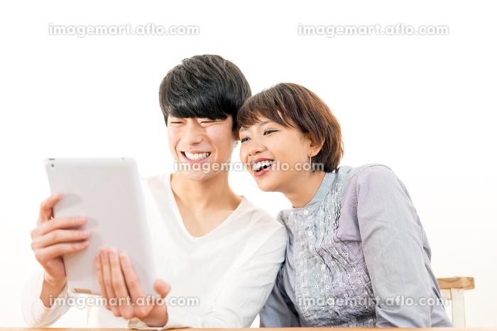 タブレットPCを見る若いカップルの販売画像