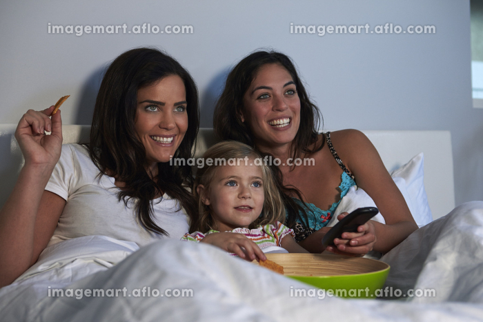 Young girl watching TV in bed with gay female parentsの販売画像