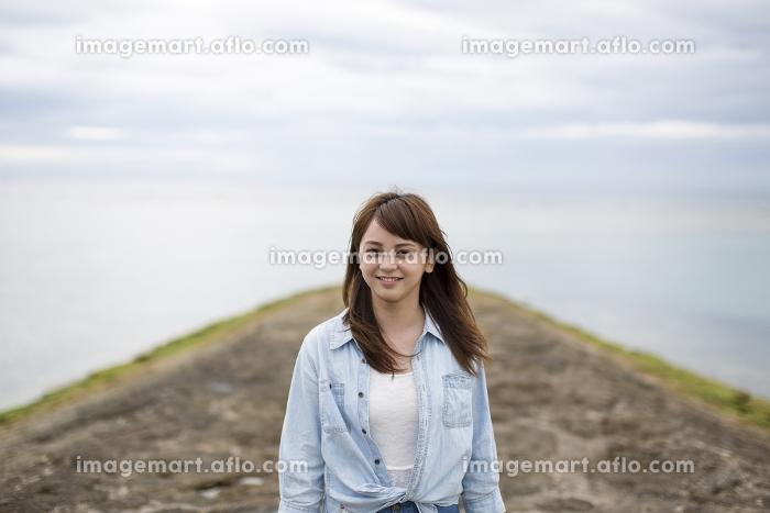 海岸に立って笑う日本人女性の販売画像